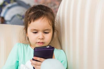 Cute little girl using modern smartphone