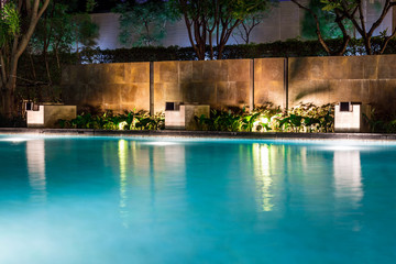 Lush pool lighting in backyard for luxury swimming pool design created by great lighting professionals.