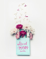 Best mom ever . Mothers day greeting card . Fresh lovely flowers in blue paper shopping bag on white desktop background, Top view , copy space
