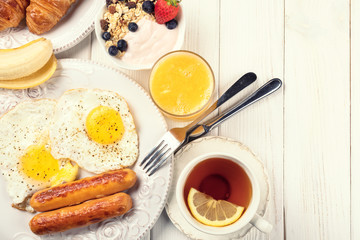Breakfast of sunny side up eggs, sausages, orange juice, tea, and fruits
