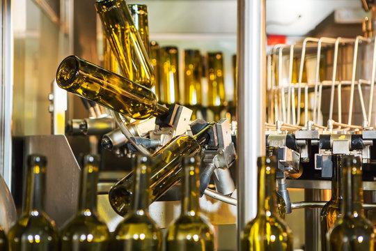 Unlabeled glass bottles in bottling machine at modern winery