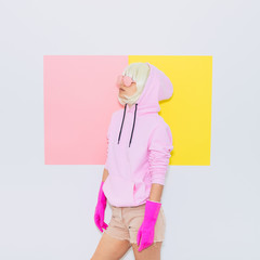 Doll Blonde Girl Model with beauty face in the hood with Fashion accessory sunglasses, gloves,  hoodie and shorts.  Mood and vibes. Minimal unicorn style. Pink and yellow neon colors. 90s or 80s trend