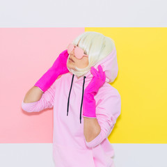 Doll Blonde Girl Model with beauty face in the hood with Fashion accessory sunglasses and gloves.  Mood and vibes. Minimal unicorn style. Pink and yellow neon colors. 90s or 80s trend