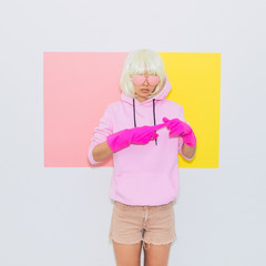 Beautiful Doll Blonde Girl Model in the hood with Fashion accessory sunglasses, gloves,  hoodie and shorts. Mood and Vibes.  Minimal unicorn style. Pink and yellow neon colors. 90s or 80s trend