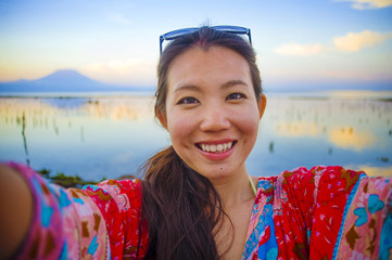 self portrait of gorgeous beautiful and happy Asian Korean or Chinese woman 20s taking selfie photo with mobile phone camera in exotic tropical beach