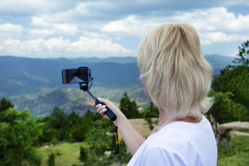 Smart phone on travel. Woman standing alone outdoor with wild forest mountains on background and doing photo of landscape.Vacation concept.