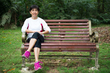 Asian senior woman relaxing on park bench