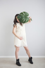 Brunette pregnant woman holding monstera leaf