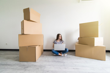 Young woman sitting on hardwood floor in new aprtmanet, using laptop next to cardboard box