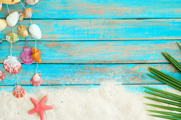 Summer background with beach sand, starfishs coconut leaves and shells decoration hanging on blue wooden background.  Summer concept, Vintage retro styles.