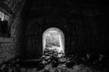 The entrance to the stone fortress is littered with stones. B/W photo