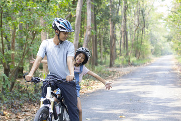 Happy father and daughter cycling in the park, togetherness relaxation concept