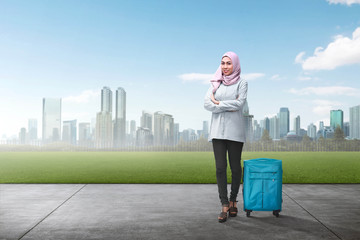 Cheerful asian muslim woman traveling with suitcase