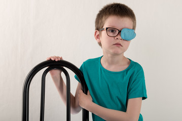 Child in glases with Occluder. .Ortopad Boys Eye Patces nozzle for glasses for treating strabismus (lazy eye)