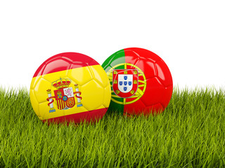 Spain vs Portugal. Soccer concept. Footballs with flags on green grass