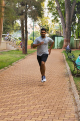 Young guy jogging on a path in a park