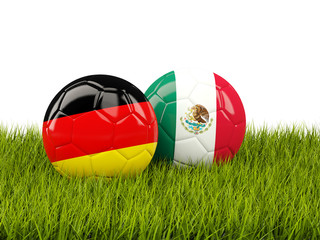 Germany vs Mexico. Soccer concept. Footballs with flags on green grass