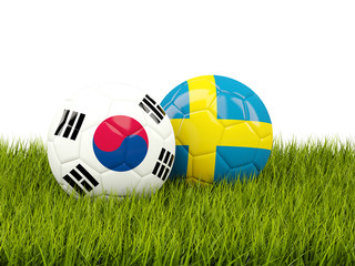 South Korea vs Sweden. Soccer concept. Footballs with flags on green grass