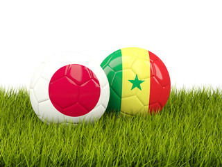 Japan vs Senegal. Soccer concept. Footballs with flags on green grass