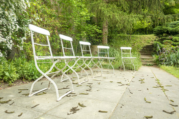 five chairs outside in the green garden