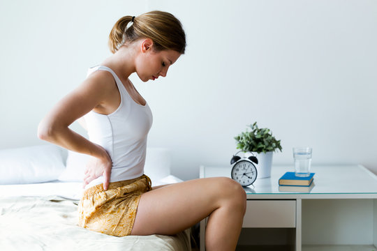 Tired young woman with back pain sitting on the bed at home.