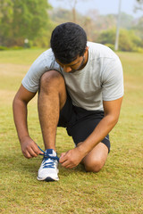 Young guy tying shoe laces and getting ready to run