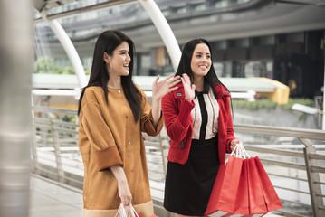 Beautiful girls holding shopping bags walking at the shopping mall.
