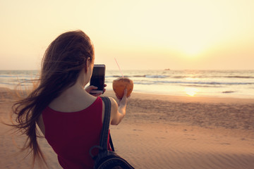 A girl is taking pictures of a coconut