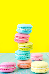 French macaron cookies on bright yellow background.Sweet dessert.