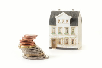 stack of coins next to a miniature old building house, real estate concept forproperty investment or rental costs for a home, isolated on a white background