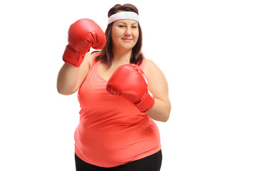 Overweight woman wearing a pair of red boxing gloves
