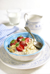 Oat porridge with fresh strawberry for a breakfast.