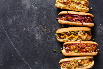 Hot dogs with different toppings on a dark background.