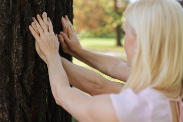 Rear view of blonde woman with man touching tree