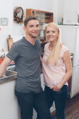 Portrait of smiling couple standing in kitchen
