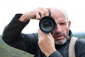 Portrait of a middle-age bald photographer with beard and leather jacket taking pictures at work with digital camera on the countryside