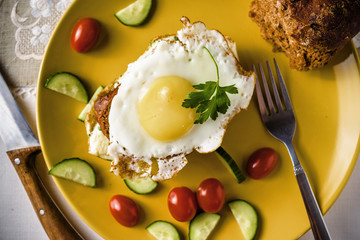 Dish of sandwich with fried eggs, cucumbers and cherry-tomatoes with bread and milk on linen tablecloth, dark and moody.