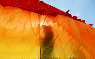 Members of People's Liberation Front party perform as they use a Chinese dragon puppet during a May Day rally in Colombo