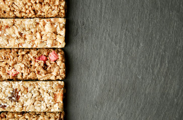 Row of mixed gluten free granola cereal energy bar with dried fruit & various nuts, gray concrete background. Healthy vegan super food, fitness dieting snack for sporty lifestyle. Top view, copy space