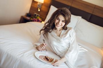 Smiling attractive girl eating breakfast