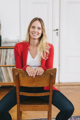 Smiling woman with red cardigan sitting on chair