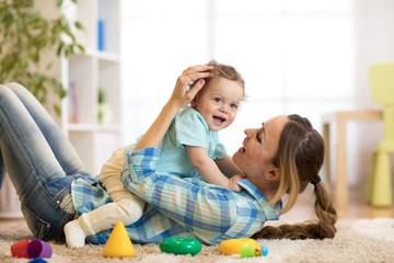 Happy mom and child son lying on the floor and playing indoor