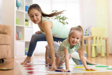 Young mother playing twister with her kids. Cheerful family at home. Happy family having a fun together.