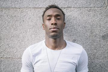 African man in white shirt posing.