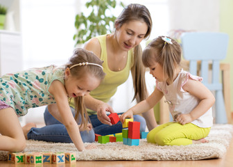 Adorable children with mother playing colorful toys