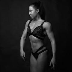 Muscular girl on a black background. Sport, fitness model.