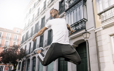 African man shirt jumping front building.