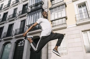 Smiling young man jumping mid air
