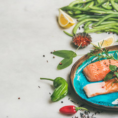 Raw salmon fish fillet steaks with vegetables, greens, rice, spices and lemon in blue plate over light grey marble background, copy space, square crop . Clean eating, alkaline diet, dieting concept