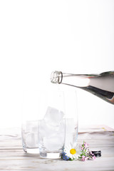 Pouring of still mineral drink water in glasses with ice cubes close up copy space